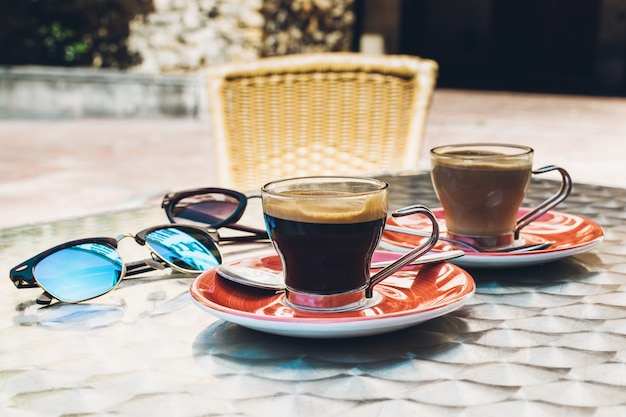 Two cups of spresso coffee at a terrace. a pair of glasses on a metal table