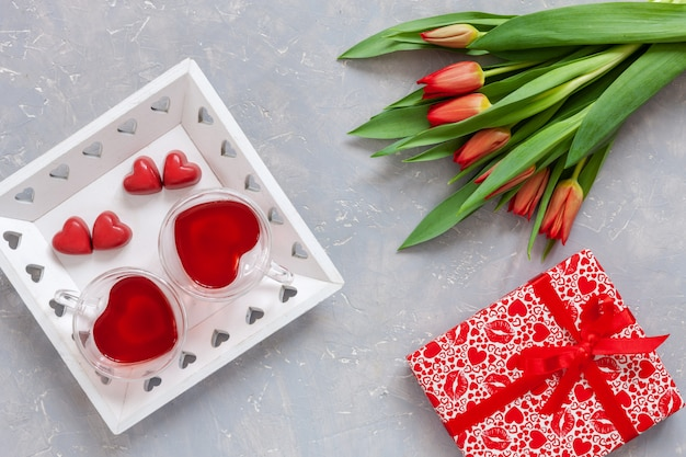 Two cups of tea, red chocolate candy, gift box with red ribbon and red tulips bouquet