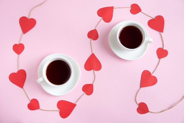 Two cups of tea with a cord decorated with paper red hearts flat lay on a pink paper background.