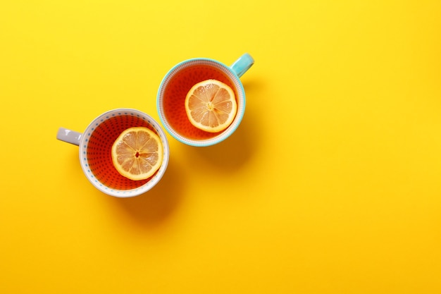 Two cups of tea with lemon on yellow background.top view, flat lay. copy space. tea for autumn or winter season.