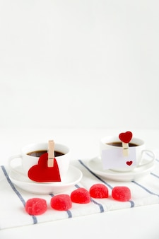 Two cups of tea with valentines and red marmalade the shape of heart on a blue-striped cotton napkin on white background with copy space.