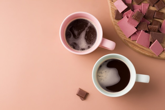 Two cups with black coffee on a brown background