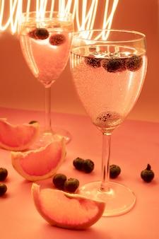 ピンク色のカクテールと動きのあるライトが付いた2つのカップ