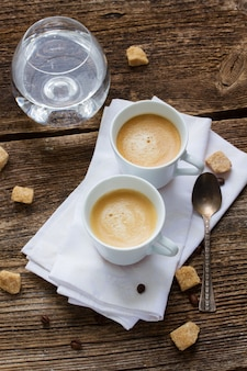 Две чашки свежего кофе эспрессо и стакан воды