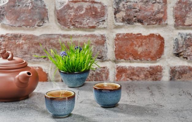 Две чашки с зеленым чаем матча на сером каменном столе, выборочный фокус. керамический чайник с чаем, пар от горячего чая поднимается над чашками, старинная кирпичная стена. крупный план, чайная церемония, минимализм