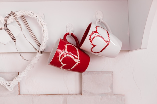 Two cups with hearts in the kitchen and a wooden white heart. valentine's day composition