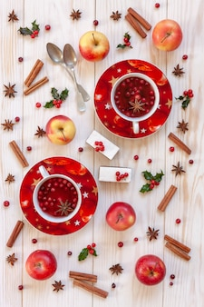 Two cups with hot christmas fruit drink with spices, berries and traditional cake slices.