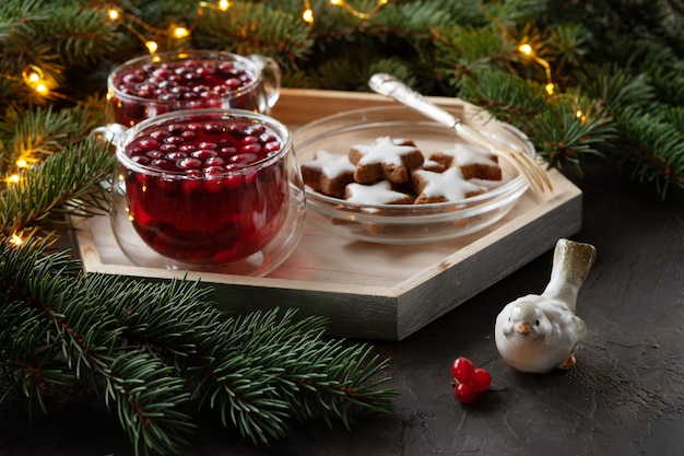 Two cups with hot christmas spicy drink with cranberry and cakes.