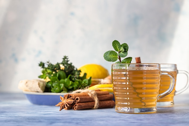 ハーブ、スパイス、レモン、生姜、蜂蜜入りの熱いお茶を入れた2杯。ミントとタイムのハーブティー。
