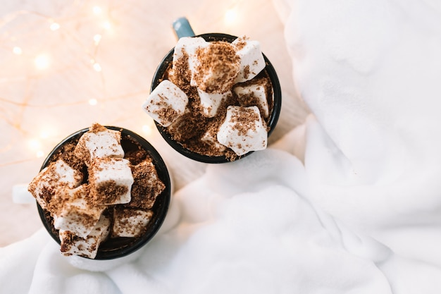 Two cups with marshmallows and cocoa powder on table