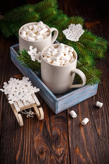 Two cups with small marshmallows on a dark wooden background