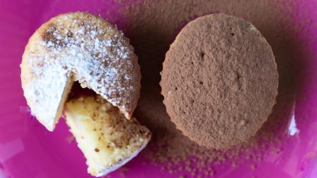 파란색 배경에 분홍색 접시에 초콜릿과 설탕을 뿌린 두 개의 두부 케이크. 디저트, 작은 컵케이크. 공기가 잘 통하는 질감의 흰색 구운 쿠키입니다. 음식 개념입니다. 위에서 볼 수 있습니다.