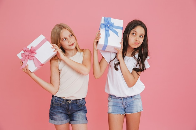 Two curious interested girls 8-10 in casual clothing holding and shaking gift boxes with colorful bows, isolated over pink background