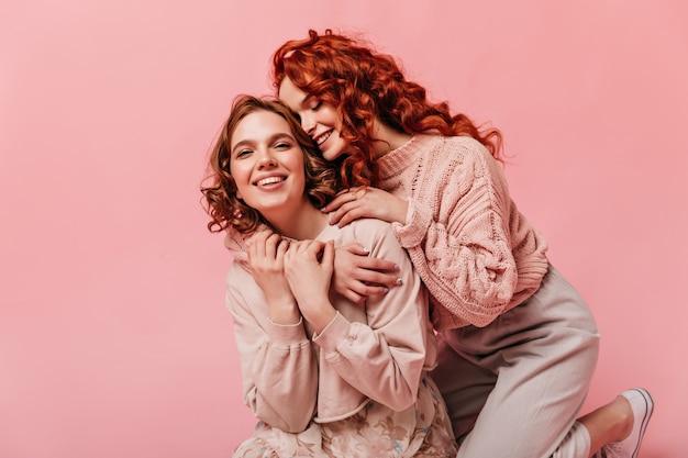 분홍색 배경에 수용 두 곱슬 여자. 행복한 친구가 함께 재미.