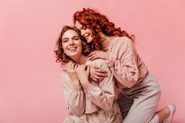 Two curly girls embracing on pink background. blissful friends having fun together.