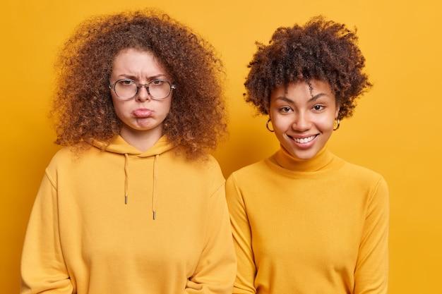 Две кудрявые женщины, стоящие рядом, выражают разные эмоции. грустная разочарованная женщина выражает отрицательные эмоции в позе рядом с лучшей подругой, которая радостно улыбается. концепция дружбы