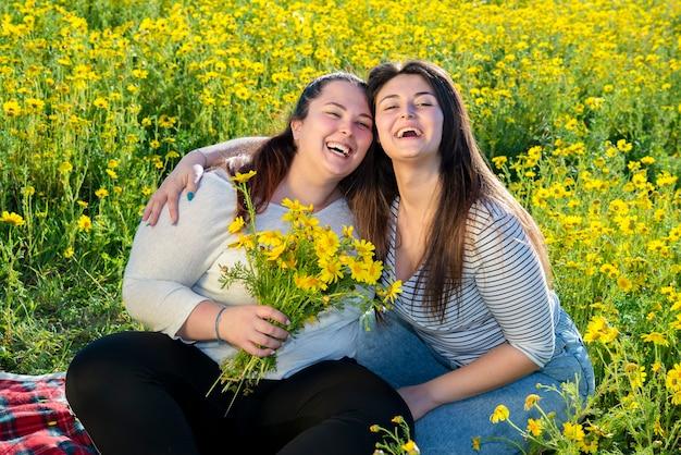 デイジーの分野で2人の曲がりくねった女の子が笑います。再開後の戸外でのんきな瞬間