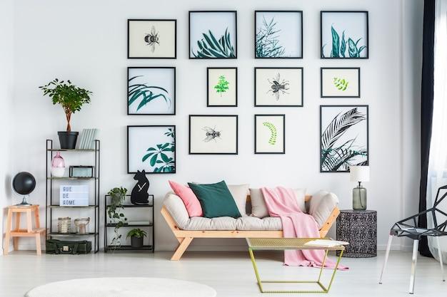 Две подушки и розовое одеяло на диване, стоящем в интерьере белой гостиной с растениями