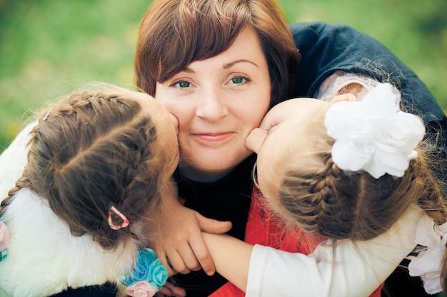 Две милые очаровательные дочки целуют счастливую маму в щеки, поздравляют маму с днем матери,