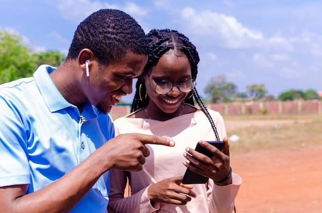 彼らは彼らの携帯電話を使用して笑っている2人のかわいいアフリカの友人