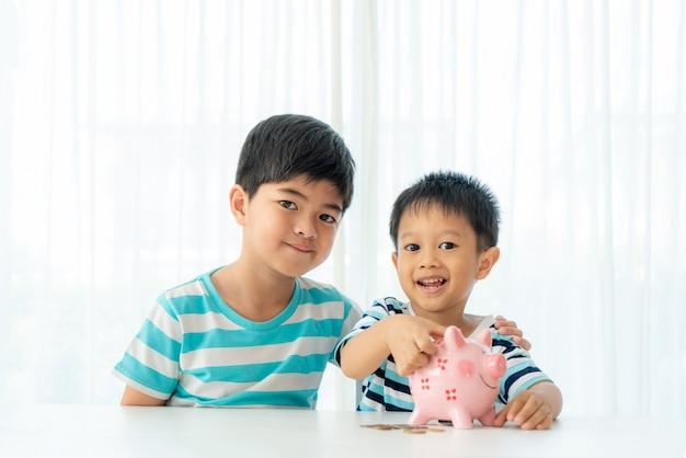 2人のかわいいアジアの兄弟が一緒に貯金箱にコインを挿入します。