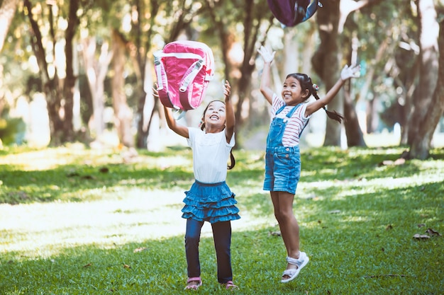 Two cute asian child girl having fun to play and throwing their backpack to the air togeth