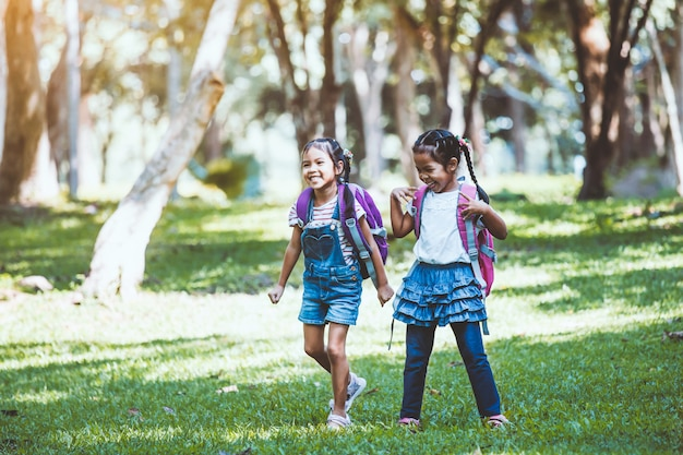 Two cute asian child girl having fun to play together in the park in vintage color tone
