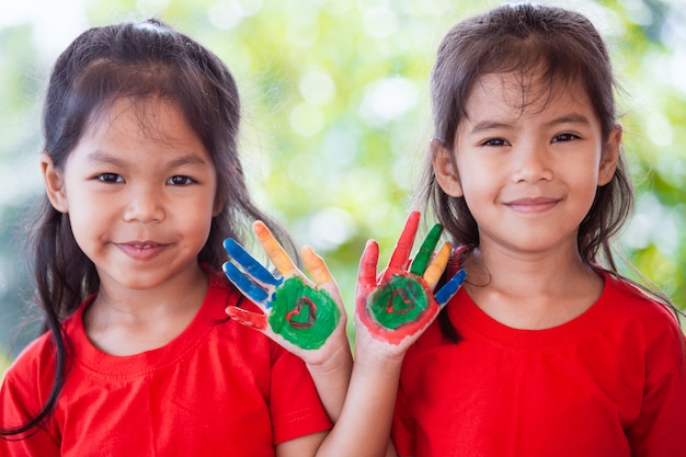 Two cute asian child girl with painted hands smiling and playing together