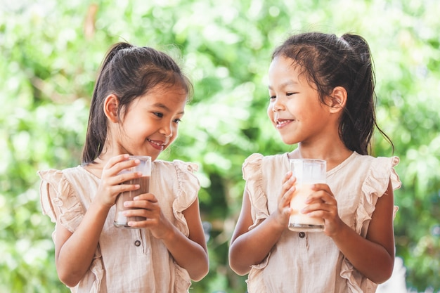 Two cute asian child girls drinking a milk from glass together
