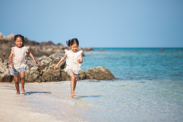 Two cute asian child girls having fun to play and run on beach together in summer vacation