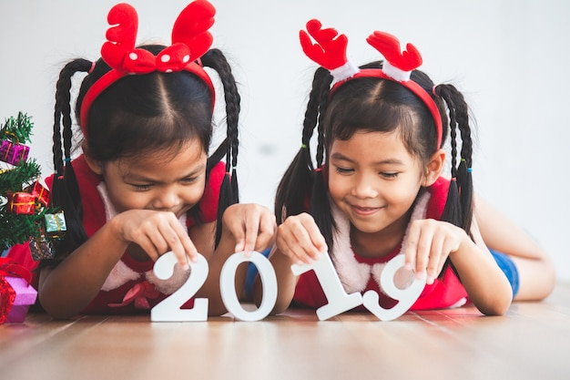 Two cute asian child girls holding numbers 2019 to celebrate new year holiday