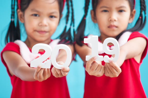 Two cute asian child girls holding numbers 2019 to celebrating new year holiday