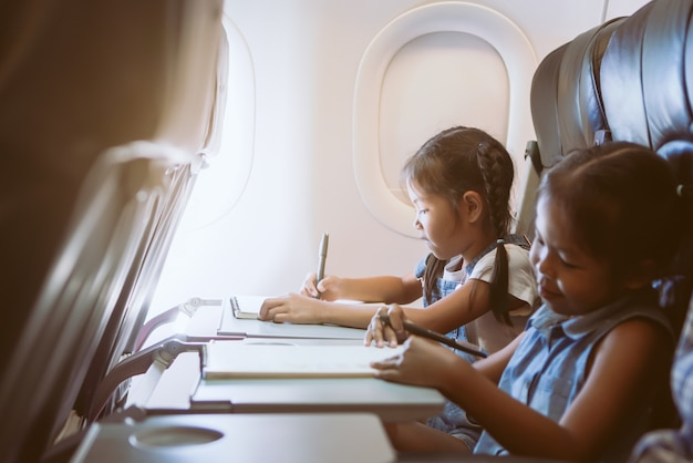 Two cute asian child girls traveling by an airplane and spending time by drawing and reading