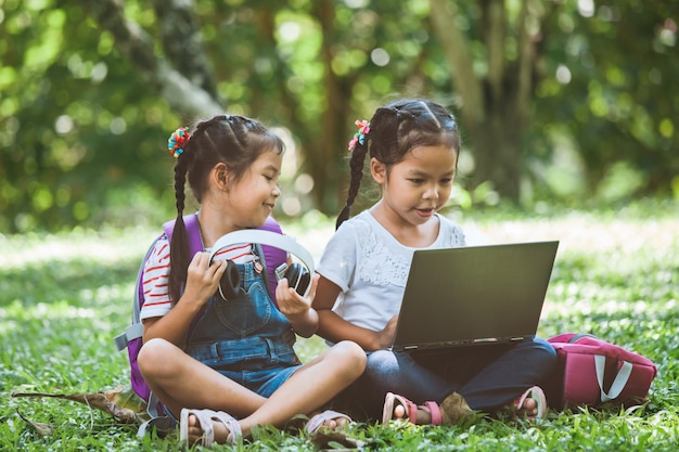 Two cute asian child girls using laptop in the park together with fun and happiness