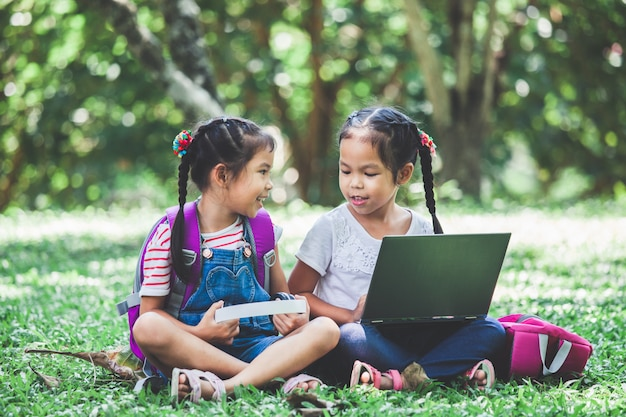 Two cute asian child girls using laptop in the park together with fun and happiness.