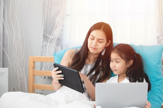 Two cute asian child girls using tablet and laptop on bed.