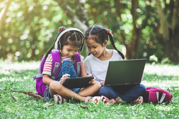 Two cute asian child girls using tablet and laptop in the park together