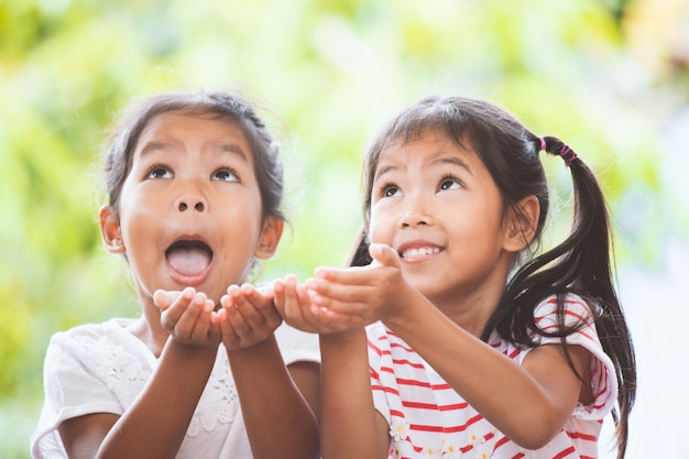 Two cute asian child girls waiting candies falling from the sky