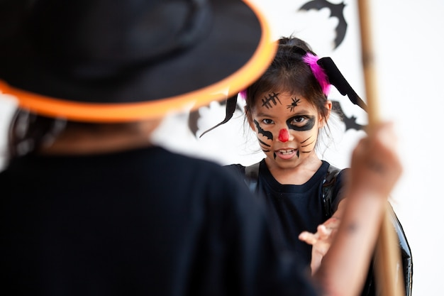 Two cute asian child girls wearing halloween costumes and makeup having fun on halloween celebration