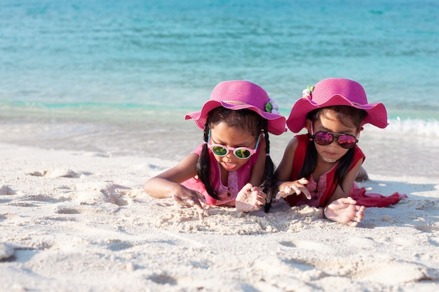 Two cute asian child girls wearing pink hat and sunglasses playing with sand together on the beach