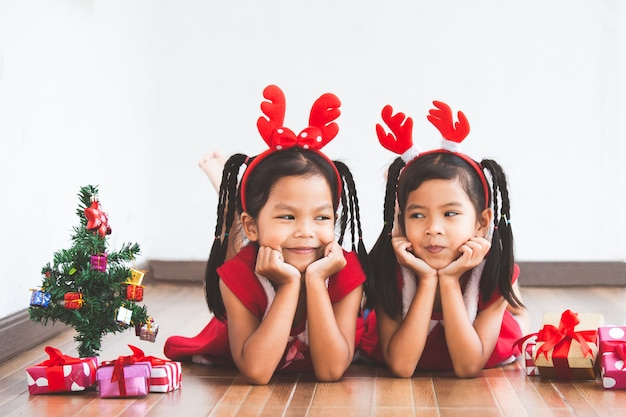 Two cute asian child girls with gift boxes and christmas tree to celebrate christmas