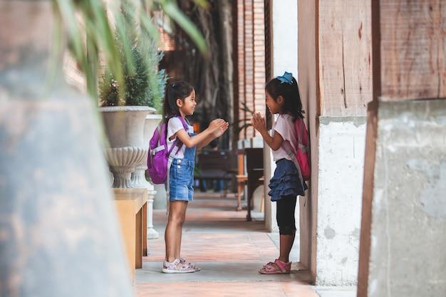 学校で放課後一緒に遊んでランドセルを持つ2つのかわいいアジアの子供女の子