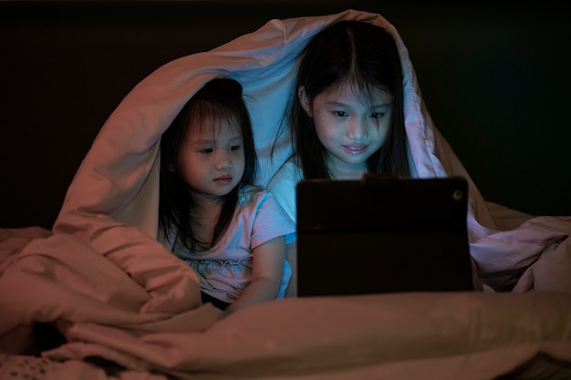 Two cute asian kids in pajamas watching cartoon movie from tablet under blanket