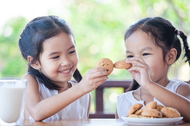Two cute asian little child girls are eating cookies with milk for breakfast