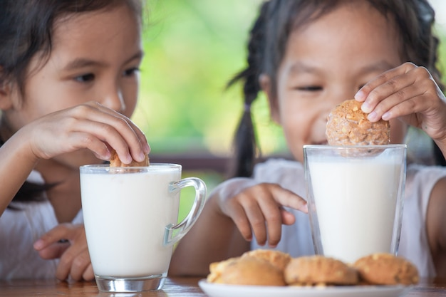 Two cute asian little child girls are eating cookies with milk