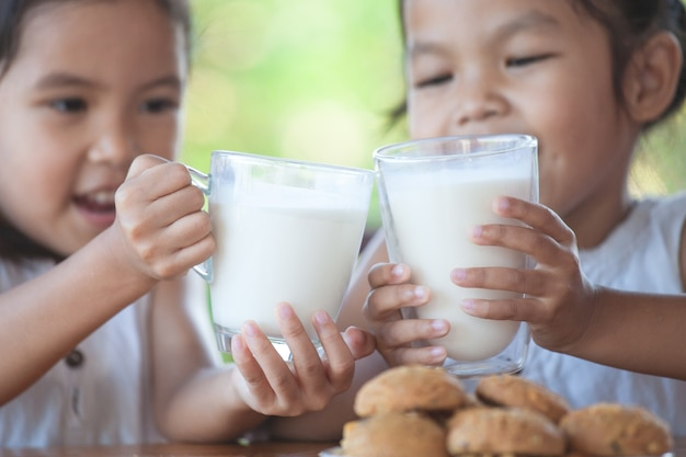 Two cute asian little child girls holding glass of milk for breakfast