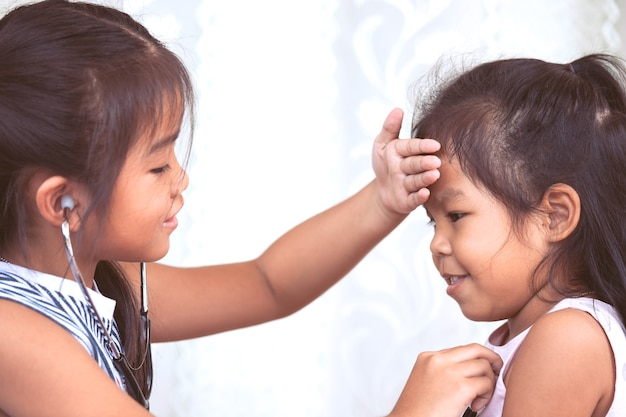 Two cute asian little child girls playing doctor and patient together in vintage color tone