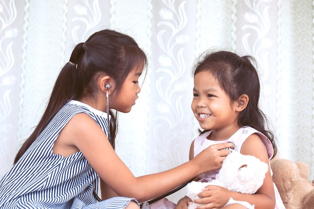 Two cute asian little child girls playing doctor and patient with stethoscope together in vintage color tone
