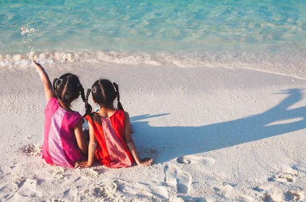 Two cute asian little child girls sitting and playing together on the beach
