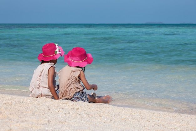 Two cute asian little child girls sitting and playing with sand together on the beach
